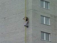 壁のパイプをつたって14、5階建てのマンションを屋上まで登る