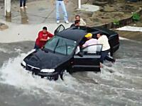 洪水で取り残された車の中から女性を救出しようとするドラマチックな映像。