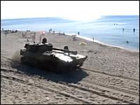 おそロシア。海水浴客で賑わうビーチをロシア軍の装甲車両の一団が通過。