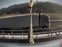 クレイジーってレベルじゃねーぞ・・・。並走するトラックの間で綱渡り・・・。