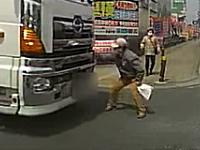 向かってきた大型トラックを右腕一本で止めようとするおじいちゃんの映像。