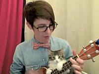 お姉さんのギター演奏を邪魔するニャンコが可愛いビデオ。これは羨ましいw