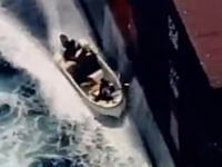 ソマリアの海賊たちが大きな貨物船を乗っ取ろうとしているシーンの映像。