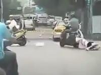 後部座席から落ちて引きずられている女の子に気づかずに走り続けるスクーター